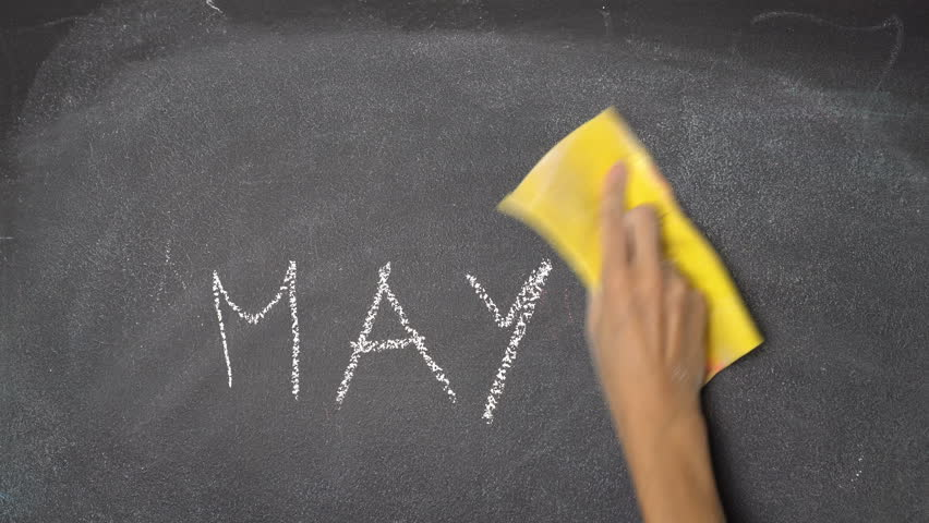 Woman's hand writing all months from January to December with white chalk on blackboard