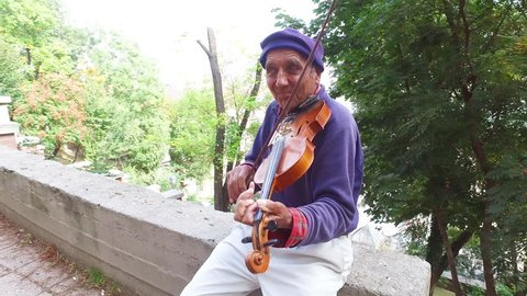 Budapest, Hungary-2010s: A colorful old gypsy man plays the violin in a park in Budapest, Hungary.