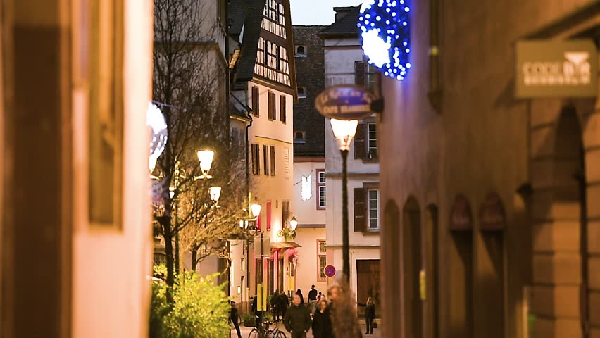 STRASBOURG, FRANCE - CIRCA 2017: Night evening with romantic street and French couples walking on the Christmas decorated winter holiday season in Strasbourg, Alsace, France