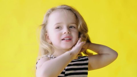 Portrait of a cute beautiful little girl with long curly hair on a yellow background, slow mo. Medium Close-Up. Pretty nice baby girl coquettishly adjusts her long hair. Child of Slavic appearance