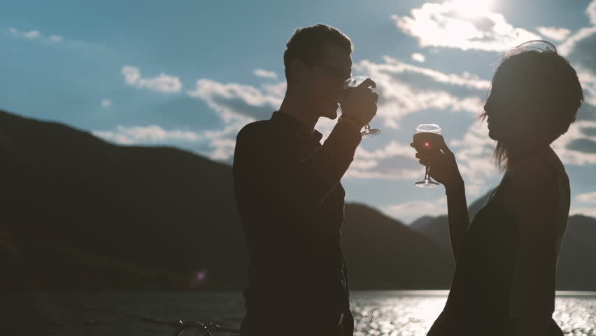 Young couple drinking wine standing on beach on summer day. Man with glasses and woman dressed in black silk gown waving by light wind located near water against backdrop of glowing turquoise waves #28689319