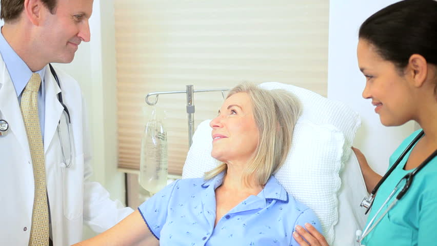 Hospital consultant nurse giving medical care to senior retired female patient | Shutterstock HD Video #2869987