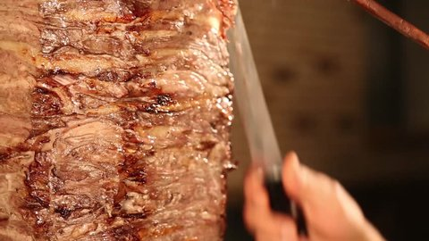 appetizing donner kebab cutting chef with tall knife, the most popular food in Turkey