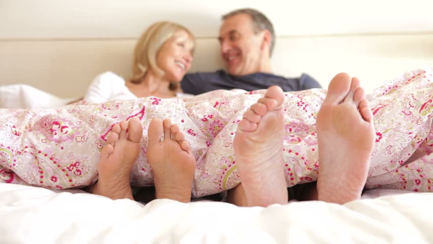 Close up of feet wriggling as senior couple sit up and chat in bed.