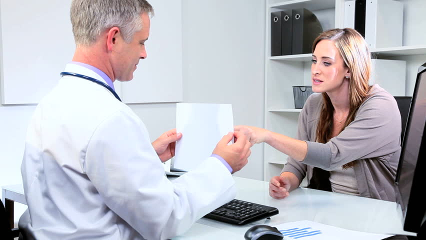 Female pharmaceutical saleswoman meeting male doctor in his office