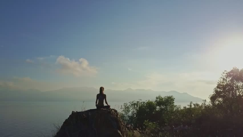 Aerial panorama boundless ocean and woman sits in Padmasana on rock under bright morning sunlight | Shutterstock HD Video #28748026