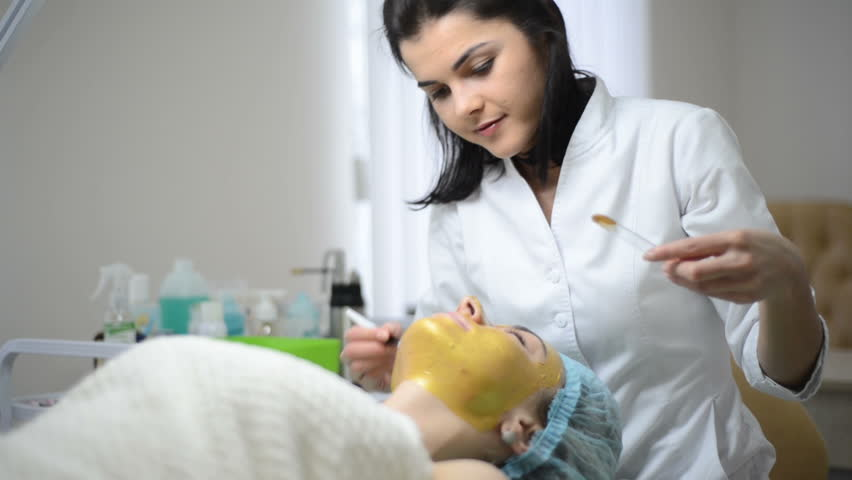 Cosmetologist applying Gold facial mask to the face, woman having cosmetic treatment at spa. Professional beautician on female at beauty salon. Skin procedures cleaning Cosmetology.