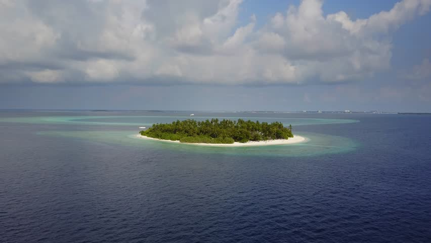 The camera moves away from round tropical atoll island resort hotel with white sand palm trees and turquoise Indian ocean on Maldives, drone footage aerial view from above in 4k