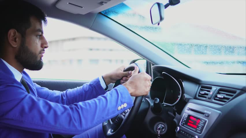 Muslim man in blue suit driving the car. Handsome serious businessman driving a car in the city | Shutterstock HD Video #28773799