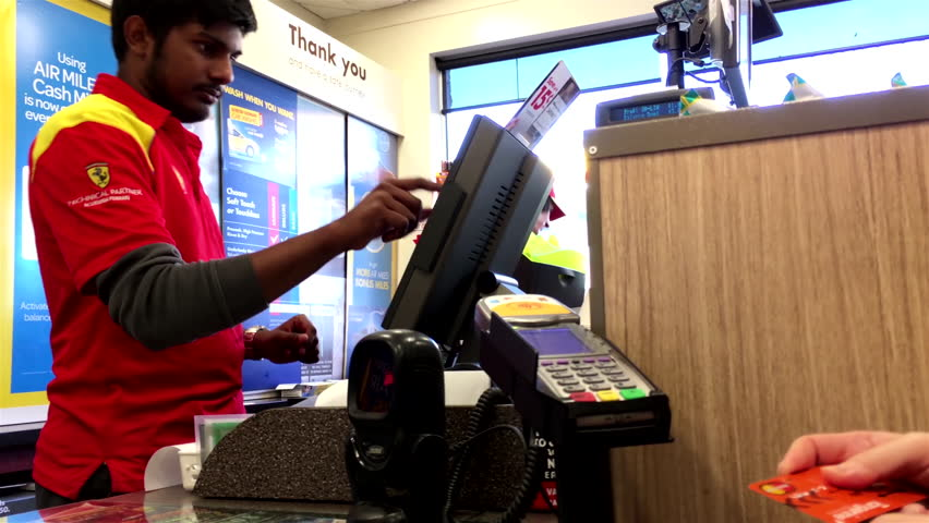 Coquitlam, BC, Canada - July 13, 2017 : Woman buying lottery ticket and tapping credit card at check out counter inside Shell gas station convenient store with 4k resolution