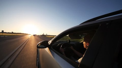left side of silvery car going toward declining sun with driver at wheel