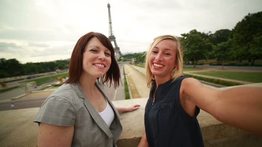 Two young women taking selfies in Paris at Eiffel tower-Summer Young cheerful women near the Eiffel tower in Paris, France taking a selfie using a mobile phone. Summer in the capital | Shutterstock HD Video #28871677