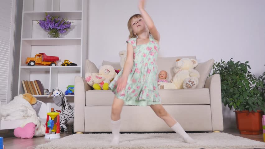 A little girl, adorable young talented dancer does ballet poses and stretching exercises on the floor at home.