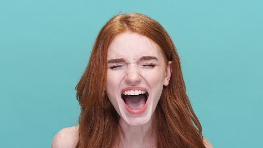 Close up of a young stressed redheaded girl shouting isolated over blue background | Shutterstock HD Video #28892719