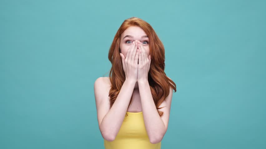 Happy young redheaded girl laughing and keeping hands at her face while standing isolated over blue background | Shutterstock HD Video #28893169