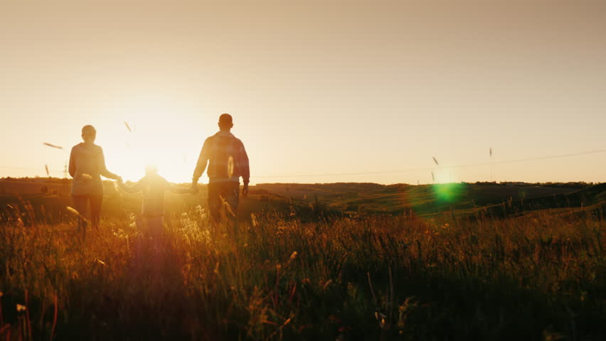 A young family of three people is going to weather the sunrise or sunset. Silhouettes, rear view. Steadicam shot | Shutterstock HD Video #28894669