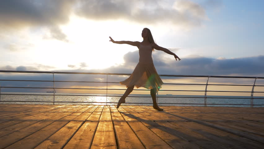 Dancing ballerina in beige silk dress and pointe on embankment above ocean or sea at sunrise or sunset. Silhouette of young woman with long hair practicing classic exercises with emotions.SLOW MOTION. | Shutterstock HD Video #28922929