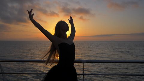SLOW MOTION. Beautiful ballerina performing pirouette. Blonde woman in black ballet tutu on embankment above ocean or sea beach at sunrise. Female dancing with arms.