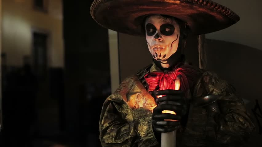 Artist with face painted like skull in Mexican Holiday Day of Dead
