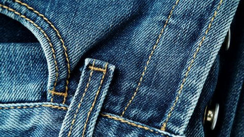 Closeup detail of blue denim jeans button zip, pocket and belt loop, texture background. Dolly sliding shot 4K ProRes HQ codec