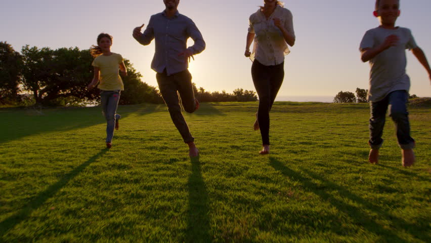 Young white family running towards moving camera in a park | Shutterstock HD Video #28929829