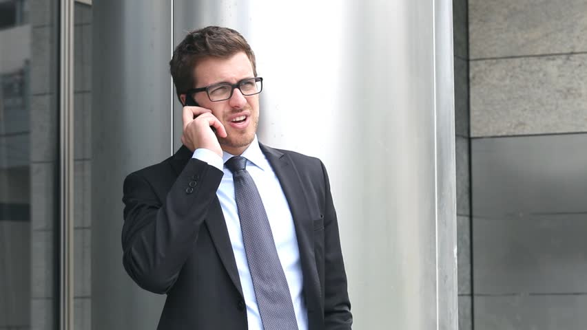 Handsome businessman talking at phone outdoor in the city