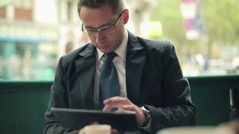 Young businessman with tablet in restaurant, outdoor