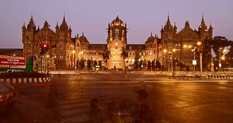 Day to night time lapse shot of traffic moving in front of Chhtrapati Shivaji Terminus (CST) formerly known as Victoria Terminus (VT) is being lit up as the night approaches, Mumbai, India
