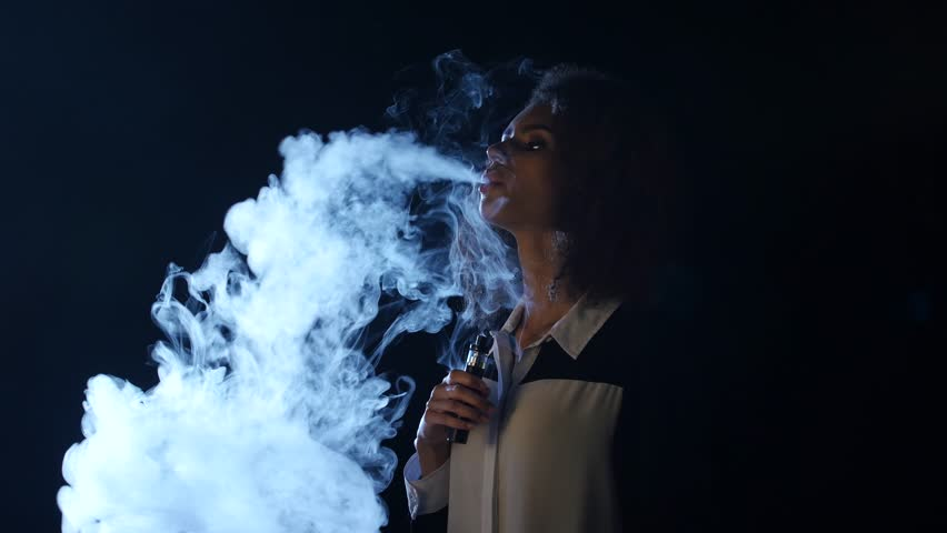 Girl inhales and exhales smoke from an e-cigarette. Black background