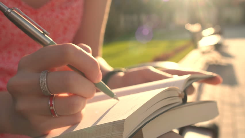 Looking up for inspiration while walking outdoor in green spring park garden. Close-up of young woman hands writing down her hopes and dreams of future into her diary, making plans. Planner To Do