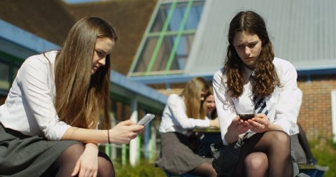 4K School girls looking at smartphones outside school building. Checking social media but not communicating with each other. Slow motion