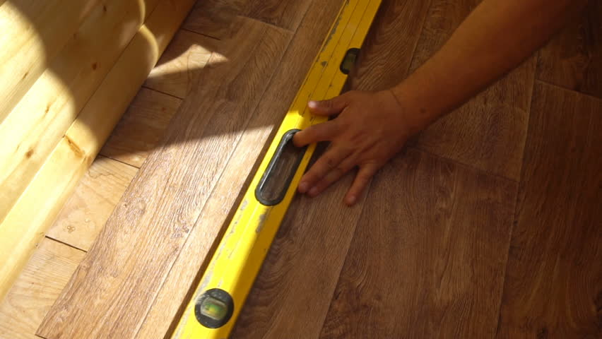 the worker cuts off the linoleum with a utility knife,fitting of linoleum floor.