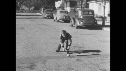 1950s: UNITED STATES: children play ball games in street. Boy hits ball. Boy runs after ball. Boy runs towards oncoming car