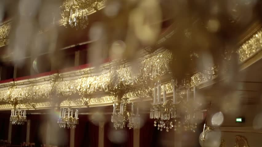 Interior of the old castle or theatre. Beautiful gallant large chandeliers with light candles and dark side background