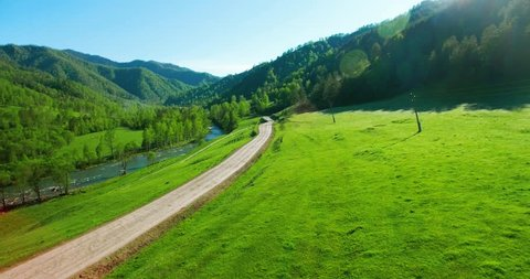 Aerial UHD 4K view. Low air flight over mountain rural dirt road and meadow at sunny summer morning. Near green trees, sun rays and mountain river