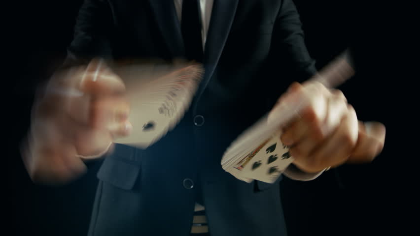 Close-up of a Magician's Hands Performing Card Tricks, Making Fan Out Cards. Magician Wears Black Suit and is Shot on Black Background. Shot on RED EPIC-W 8K Helium Cinema Camera.