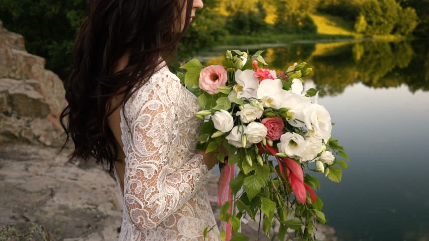 Young bride holding wedding bouquet on the river bank, close-up, sunset | Shutterstock HD Video #29106835