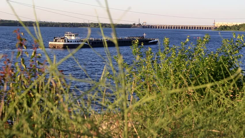 Against the backdrop of grass and trees, far away, along the river a long barge is moving towards the dam | Shutterstock HD Video #29130649