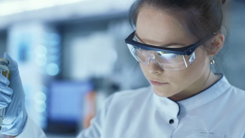Female Research Scientist Uses Micropipette Filling Test Tubes in a Big Modern Laboratory. In the Background Scientists are Working. Shot on RED EPIC-W 8K Helium Cinema Camera.
