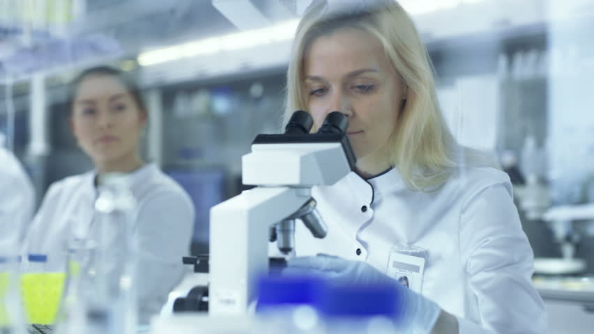 Female Research Scientists Passes Slided to Her Colleague Who Observes Sample under Microscope. They Work in a Big Research Center/ Laboratory. Shot on RED EPIC-W 8K Helium Cinema Camera.
