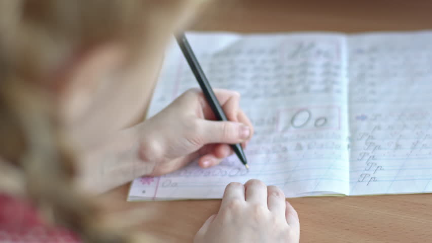 Over the shoulder shot with PAN of unrecognizable little girl with braided hair practicing writing letters in notebook | Shutterstock HD Video #29136769