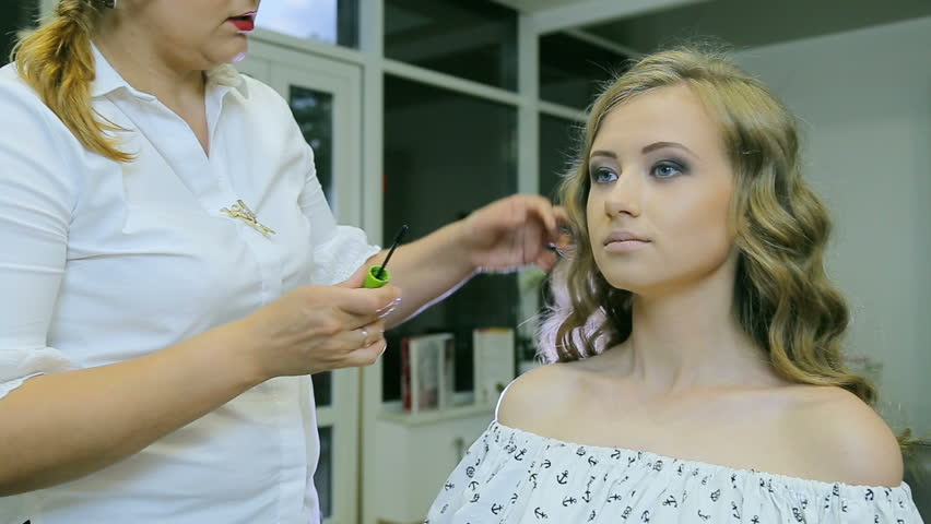 Professional makeup artist applying mascara models eyelashes. Young attractive girl with long curly blond hair and blue eyes. | Shutterstock HD Video #29167399