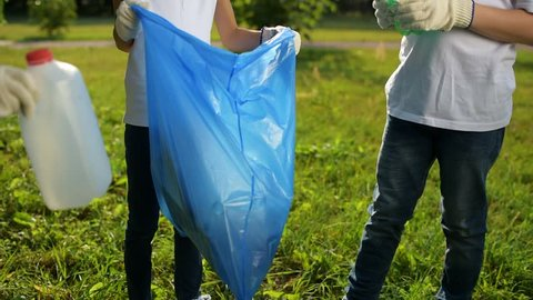 Charming kids working together while picking up garbage in park