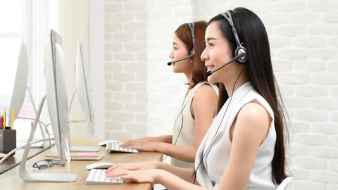 Happy beautiful Asian telemarketing customer service agent team working in the office, call center job concept