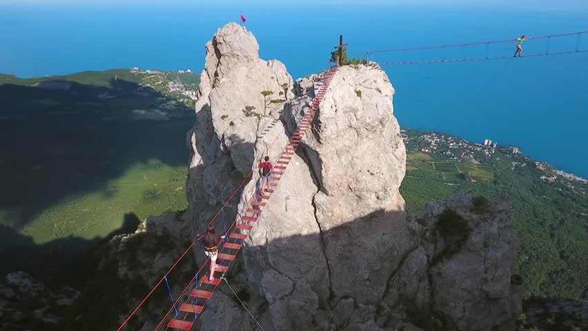 Aerial: Young Extreme Hiker Man Walking on a Suspension Bridge. Popular Russian Touristic Mountains Ai-Petri, Crimea. Black Sea Coast and Yalta City on Backgroung. HD.