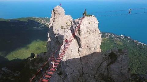 Aerial: Young Extreme Hiker Man Walking on a Suspension Bridge. Popular Russian Touristic Mountains Ai-Petri, Crimea. Black Sea Coast and Yalta City on Backgroung. HD.