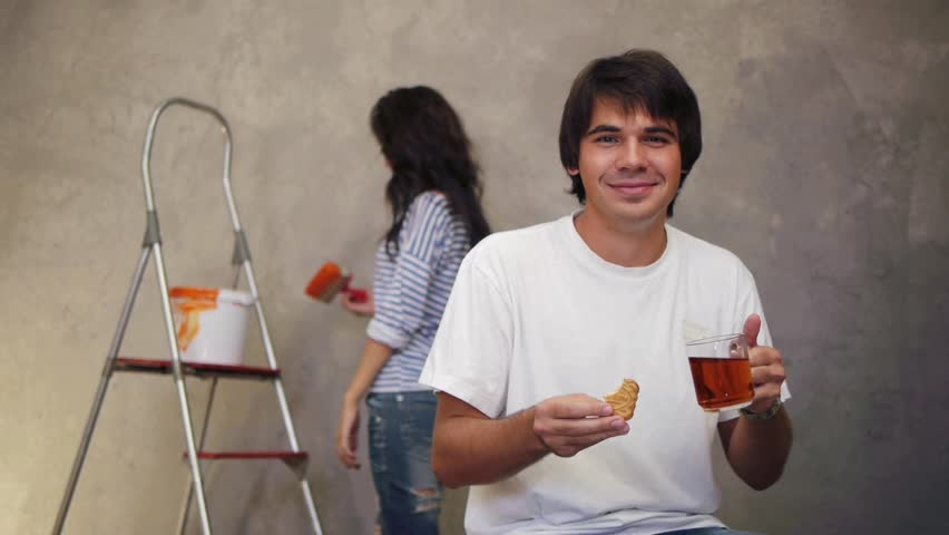 Attractive man drinking tea while his wife working
