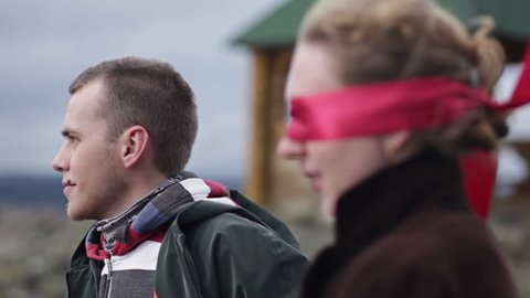 Man taking off bandage from woman's head