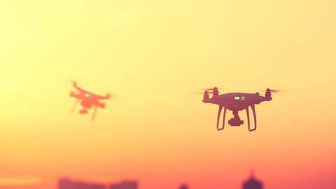 Two Professional Remote Control Air Drones with action cameras flying in dramatic sunset sky. Modern technologies. Travel, hobby, inspiration. Pastel orange toning. Cityscape background. Kiev, Ukraine