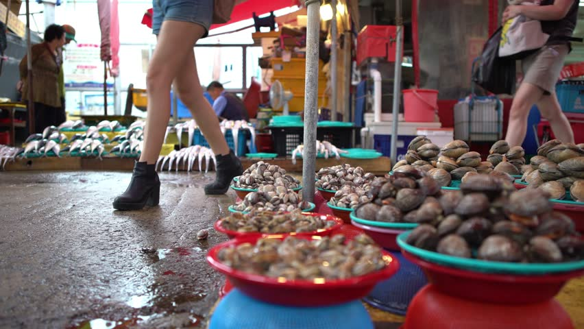 4K, South Korean Seller On Jagalchi Fish Market. Vendors and Asian People In The Seafood Market Sell And Buy Fresh Food In the street in Busan, South Korea. Selling Fresh Chilled Octopus and Clams-Dan